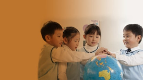 Four curious young students gathered around a globe