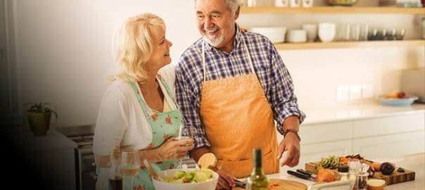 Two older people in a kitchen cooking food