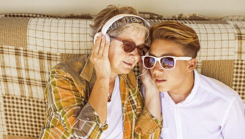 Older woman listening to music with grandson