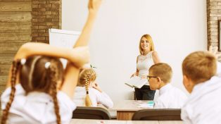 Teacher looks at student sticking hand up in the classroom