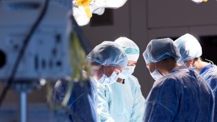Surgeons operating in theatre