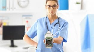 Female doctor holding out an EFTPOS machine for payment