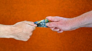 An older hand and a younger hand grappling for Australian money