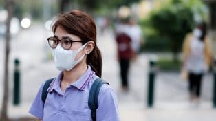 Woman walking on street wearing face mask