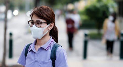 Woman walking on street wearing face mask
