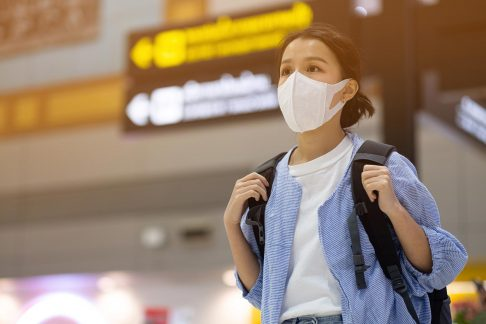 Young female traveller at airport with facemask