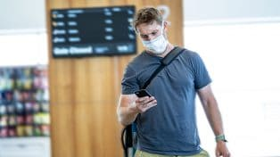 Man looking at his phone at the airport while wearing face mask