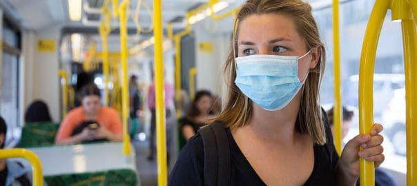 Young woman wearing a face mask on Melbourne tram