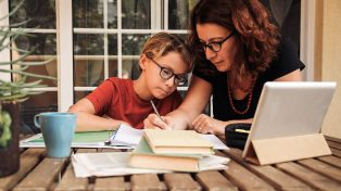 Mother home schooling child with iPad
