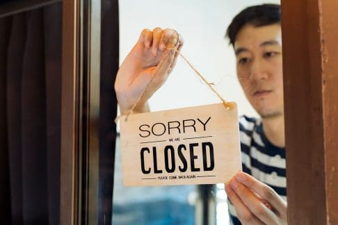 Asian man turning around business closed sign