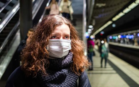 Woman wearing face mask on train station to protect from coronavirus