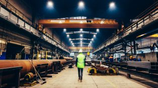 Man walking through factory wearing hi-vis