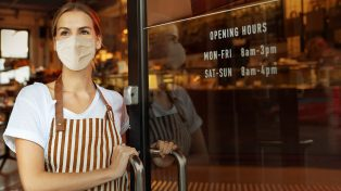 Woman wearing apron and facemask opening up cafe for business
