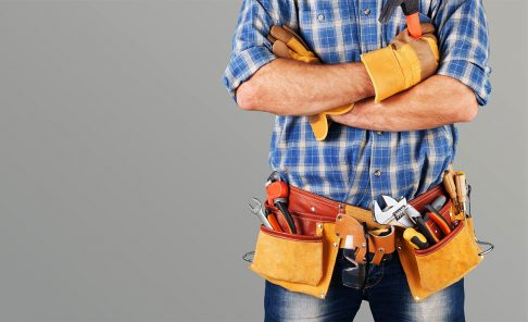 Handyman wearing tool belt with crossed arms