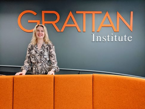 Grattan Institute CEO Danielle Wood in front of Grattan Institute sign