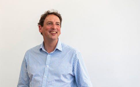 Grattan Institute CEO John Daley smiling in a blue shirt