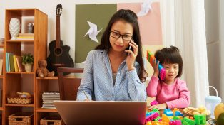 Woman working from home with young daughter next to her on play phone