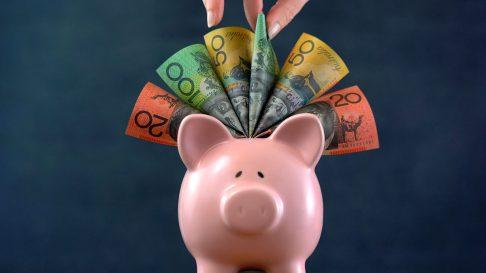 Hand pulling australian money out of a piggy bank
