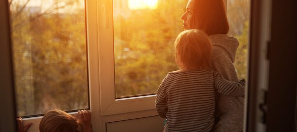 Woman at home with two children staring out the window