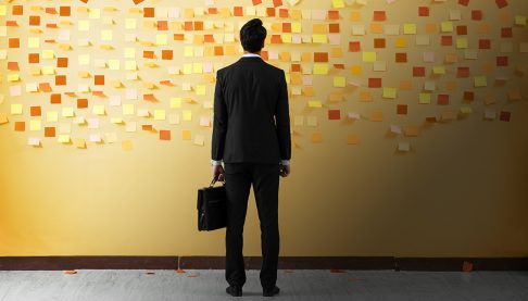 businessman standing in front of wall of post-it notes