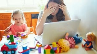 Woman working at home exhausted with small child beside her