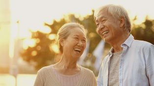 An older Asian couple laughing outdoors