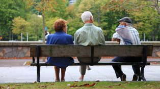 Older people sitting on a bench in a park