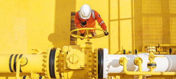 Energy gas worker in hi-vis turning pipe