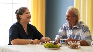 Older man talking with health worker at kitchen table with food