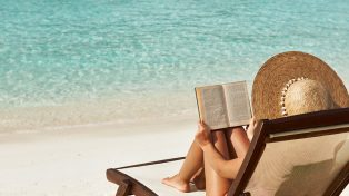 Woman laying on the beach reading a book