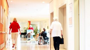 Senior walking through nursing home corridor