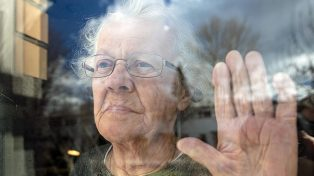Senior woman looking out window with hand to glass