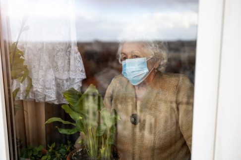 Senior woman wearing a mask staring out the window
