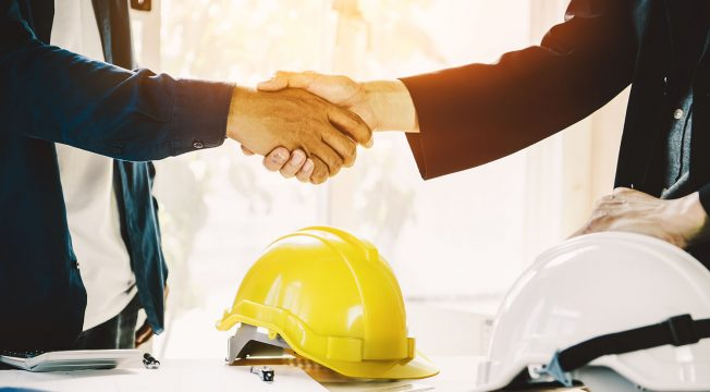 Two men shaking hands over a construction deal with a hard hat in foreground