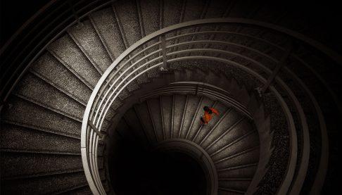 Woman in gym clothes descending a dark spiral staircase