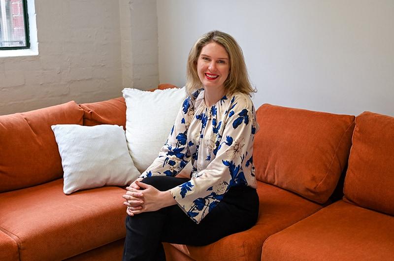 Grattan CEO Danielle Wood sitting on orange couch